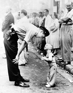 """""""Faith and Confidence,"""" photographed by William Beall for the Washington Daily News was the 1958 Pulitzer Prize winner for photography. This image was taken during the Chinese Merchants Association Parade in Washington DC. A young boy stepped into the street in front of a dancing dragon, and a tall policeman cautioned him to step back for his safety."""