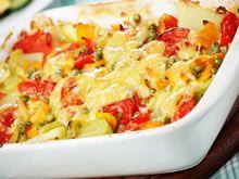 Verwarm oven op 220°C. Smelt boter in wok en roerbak ajuin + paprika (5-10 min). Doe er een groentebouillonblokje bij en roer door de groenten. Beboter een ovenschotel en doe er de voorgekookte aardappelen+gewokte ajuin en paprika+voorgekookte wortelschijfjes+ voorgekookte erwtjes+rauwe stukjes bleekselder in. Schep de groenten wat door elkaar. Strooi de geraspte emmentaler over de ovenschotel met groenten en kruid met peper uit de molen. Zet de groenteschotel met kaas 20 min in de oven.