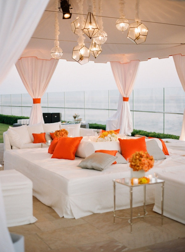 Bright orange pillows and assorted glass lanterns brought simple style to an outdoor cabana tent at @Mandy Dewey Seasons Resort the Biltmore Santa Barbara.