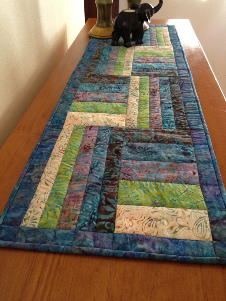 Nice Batik table runner.I've got a colourful batik jelly roll that would make up nicely into a runner like this.