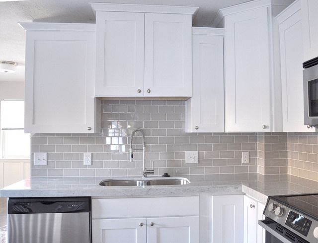 White shaker cabinets, gray glass subway tile backsplash