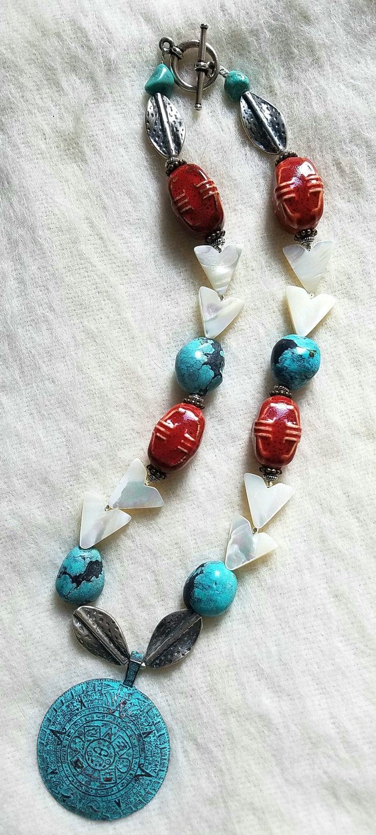 "My first thought was, ""boy those red ceramic beads are big, what am I going to make with those?!"" I thinking about making a choker style necklace and pulled out large nuggets of turquoise from my stash (can you tell I like turquoise from what I'd made so far?). Then I pulled out some mother of pearl arrows and pewter ovals. While I was moving bits and pieces around, I remembered I had a Mayan inspired pendant I'd received in another swap, and then my necklace was no longer a choker necklace."