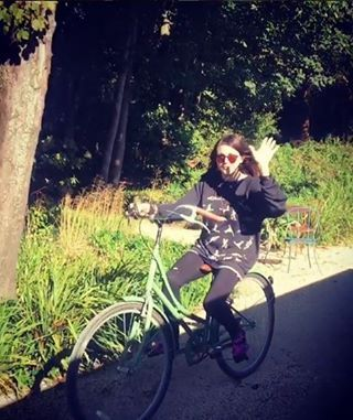 Frances Bean Cobain riding a bicycle in English countryside, 2016