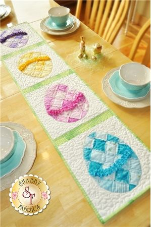 Ruched Easter Egg Table Runner Pattern: Add some sparkle to your Easter table with this beautiful Easter Egg Runner! This pattern shows you to make this quick and easy project featuring patchwork eggs, ruched ribbon and hot fixed crystals. Finished size is 12 1/2