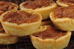 These Butter Tarts consist of flaky pastry shells that are filled with a sweet mixture of butter, brown sugar, and eggs.