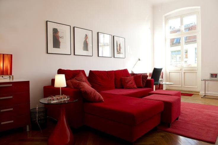 Schönes Wohnzimmer in Rot mit roter Couch, Kissen sowie rotem Teppich in Berlin. Wohnen in Berlin. #Berlin #Couch #rot #livingroom