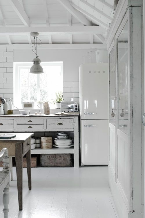 Airy Industrial #Kitchen #design #interiors white Smeg, white subway tile(with dark grout), wood floors painted with Farrow and Ball paint in some lovely white shade, open storage to display my white le creuset collection, industrial lighting, an airy feel...the bones of my kitchen.