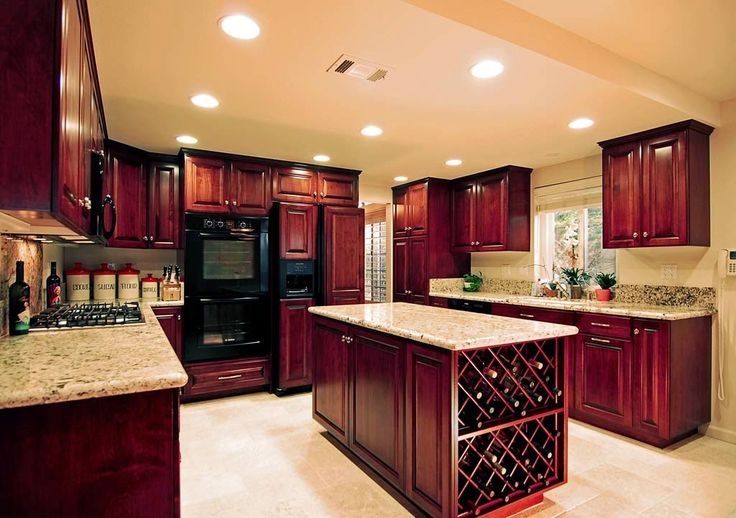 Stained Cherry Wood Cupboards Feature Granite Countertops In The Kitchen With Wine Storage In Island
