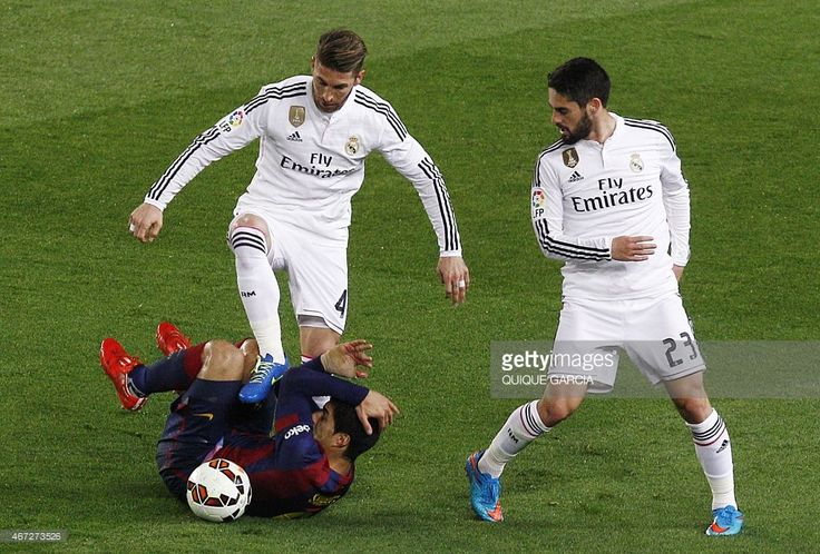 Real Madrid's defender Sergio Ramos (UP) vies with Barcelona's Uruguayan forward Luis Suarez (DOWN) as Real Madrid's midfielder Isco looks on during the 'clasico' Spanish league football match FC Barcelona vs Real Madrid CF at the Camp Nou stadium in Barcelona on March 22, 2015.