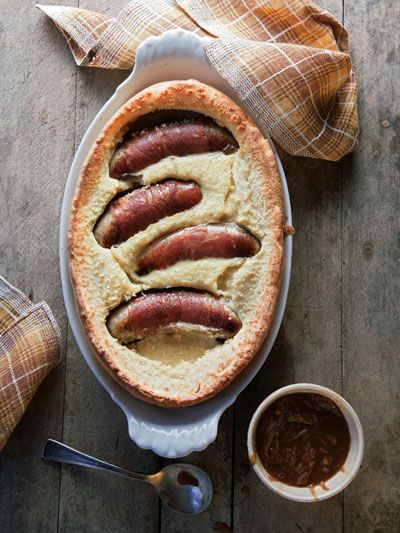 Toad in the Hole Recipe - Onion gravy is a delicious match for this comforting dish of sausages baked in a Yorkshire pudding batter. Saveur.com