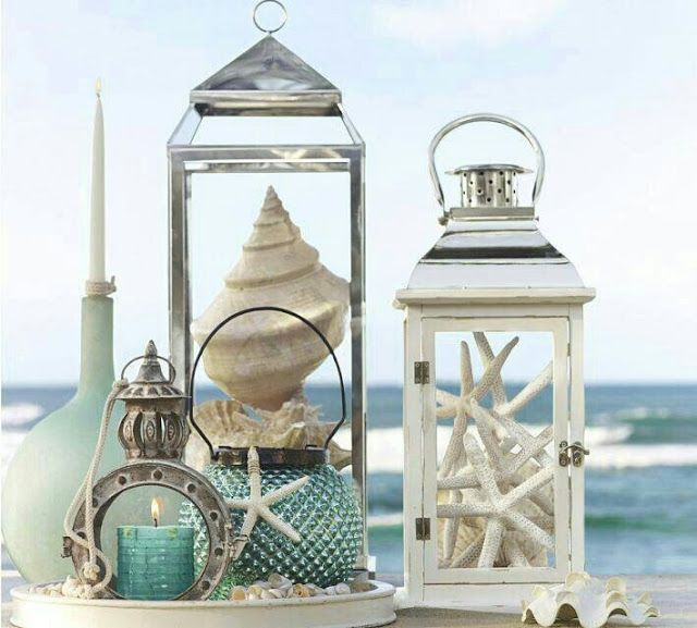 Seashells and starfish in empty lanterns or candle holders for beachy flair