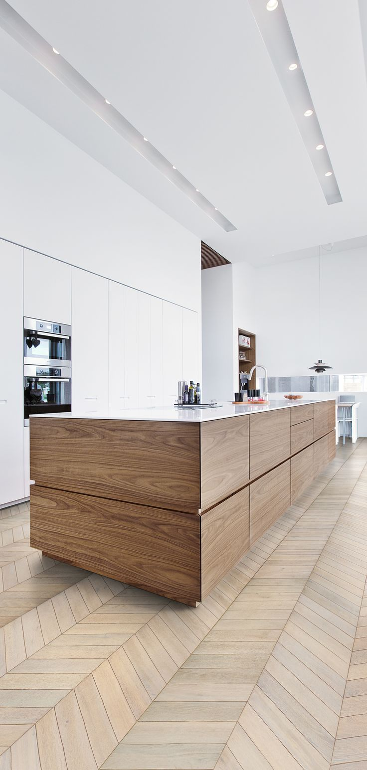 chevron white oak floor in kitchen with white modern cabinets without pulls