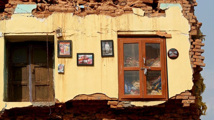 Framed pictures are seen hanging from the wall of a house damaged by earthquakes in Sindhupalchowk district, Nepal, May 13, 2015. REUTERS/Ahmad Masood