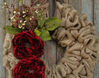 This beautiful Christmas wreath will add a rustic elegance to your home this holiday season. Natural colored burlap looped onto a wire frame creating a full wreath. 2 full deep red peonies are accented with deep red, champagne, and ivory berries, rusty stars, and greenery creating a gorgeous Christmas wreath. Hangs by either a red or brown faux burlap ribbon (choose ribbon color at time of checkout). Our wreaths make beautiful and unique gifts for Christmas, birthdays, weddings, or just…