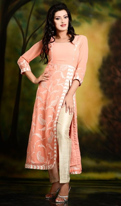 Anarkali inspired thread embroidered paisley patterned peach georgette long tunic has stylish cut in the front. Off white thread embroidered jaal pattern adorn the tunic all over. This tunic can be worn with straight pants or leggings to give it stunning look. #ExclusiveTrendsetterTunic