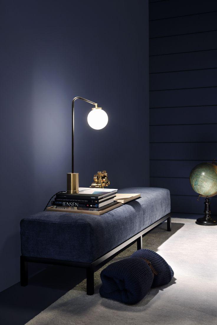 Midnight blue interior design with velvet bench and designer light