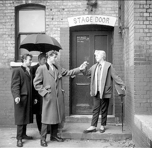 Teddy boys and girl photographed by Ken Russell, 1950s.- teddy boy styles includede long jackets with loose jackets with wide shoulders and trousers that were narrower