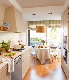 Cocina pequeña con muebles panelados en madera, office con sillas Eames, lámpara de fibra natural y estores a rayas