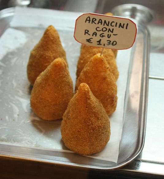 Arancini con Ragu in Sicily, Italy.They are essentially fried rice balls, filled with thick meat sauce, green peas, and sometimes cheese. YUM!