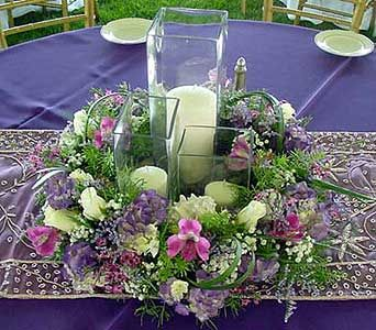 Table centerpiece with three candles and purple Hydrangea, pink Wax Flower, white Roses, Babies Breath, Caspia and purple Alstroemeria.
