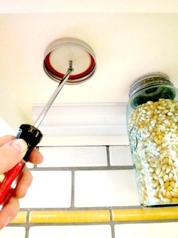 Fixe as tampas de jarros de conserva na parte inferior de seus armários para armazenamento decorativo. | 21 truques estranhos de decoração de casa que podem realmente funcionar