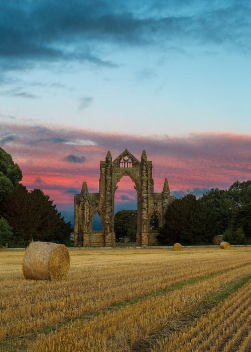 Newly baled hay lies near ruins of the  Gisborough Priory, North Yorkshire - by Paul Weller
