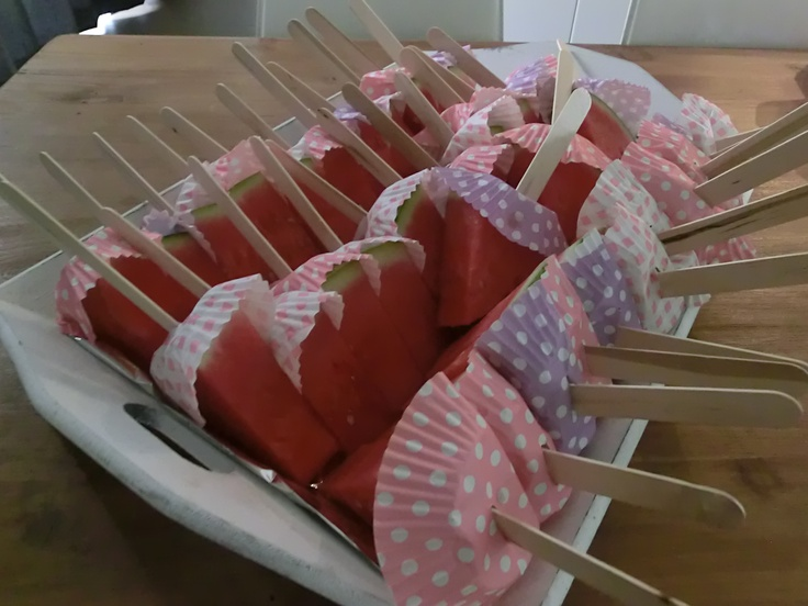 Watermeloen op een ijsstokje. Een lekkere en gezonde traktatie op een warme dag. Ijsstokjes kan je bij hobby-winkels kopen, vrolijk cupcake-papiertje erbij maakt het feestelijk.