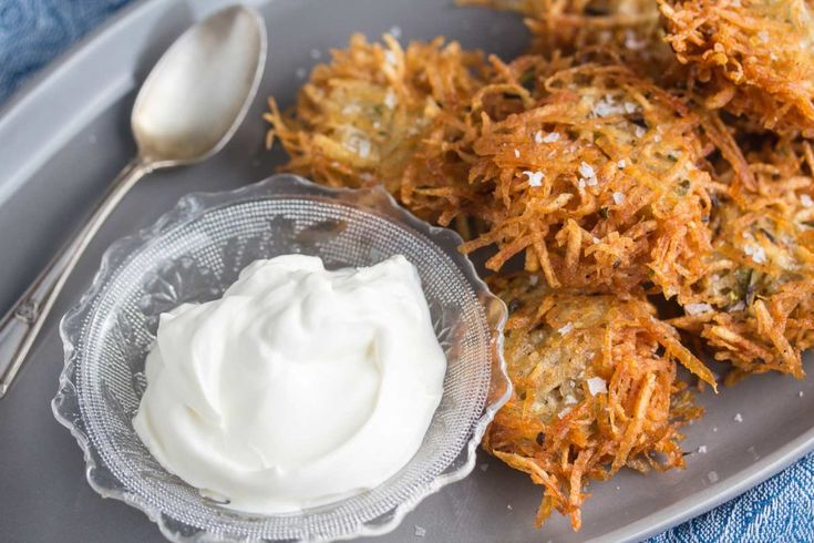 closeup shot of potato latke with flaked salt on a grey oval platter with lactose-free sour cream