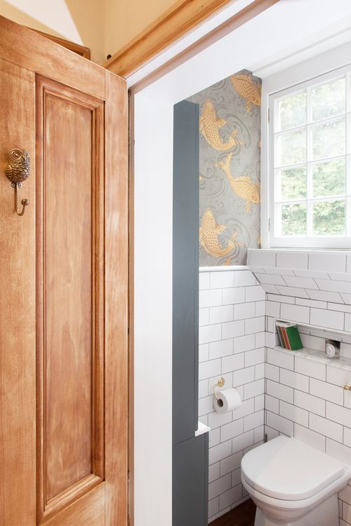 Metro tiles and Osborne & Little koi carp fish wallpaper in this small family bathroom in The Pink House