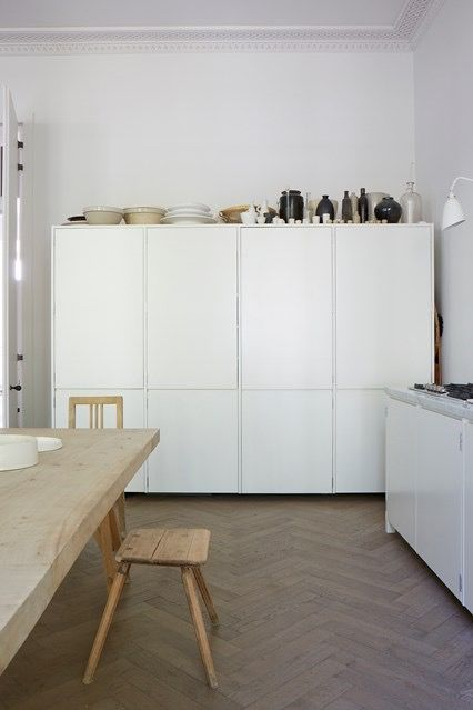 Kitchen with plain white units and beautiful old wooden herringbone parquet flooring