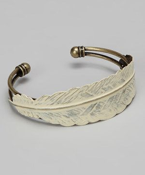 Slip this vintage-inspired cuff onto the wrist for an utterly charming look. A painted feather wraps gracefully around an antiqued brass bracelet.
