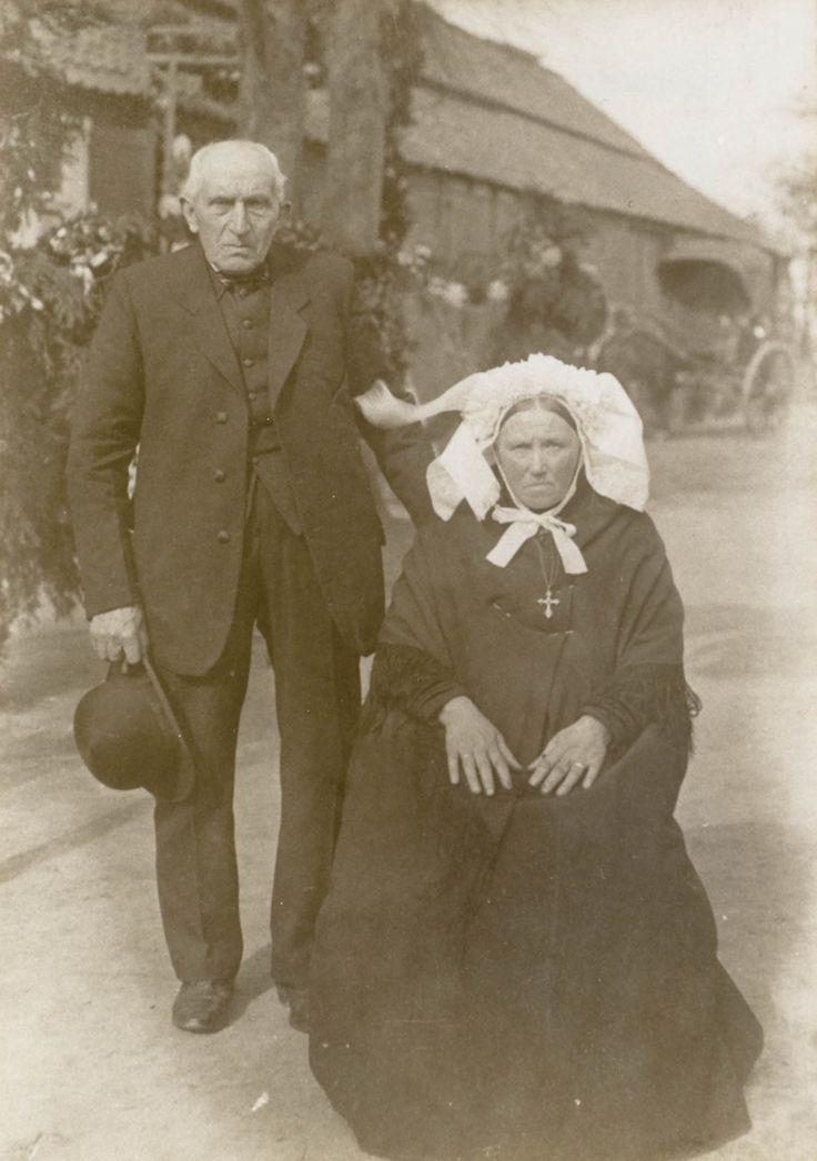 Gouden bruidspaar in streekdracht uit Ospel. De bruid draagt een zwarte japon en een 'tipdoek' met franjes. Op het hoofd draagt ze een muts met gepijpte voorstrook en een kantstrook langs de staart. Op de muts draagt ze een 'toer' van kunstbloemetjes, kunstblaadjes en linten. Sieraden: een kruisje aan een dubbele ketting en twee ringen. De bruidegom is gekleed in een ouderwets modekostuum, met een hooggesloten vest. Onder de kin draagt hij een geruit strikje. ca 1922 #Limburg