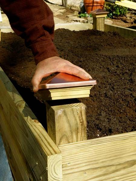 Add post caps to the corners of the raised bed.