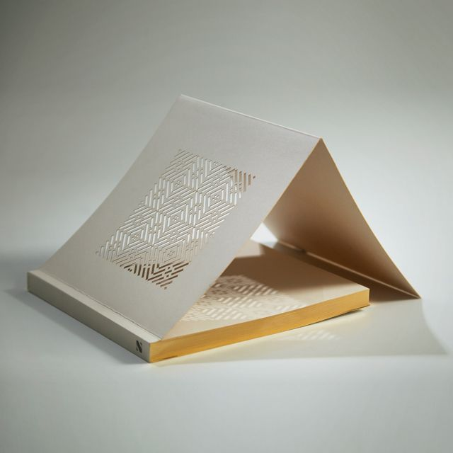 These diecut notebooks are inspired by the Mashrabiya, the latticework feature traditional to Islamic architecture. When hit by the light, the pattern forms a play of light and shadows, gracefully blanketing the surface.  The notebook is made from FSC certified paper, and has artisanal gilt-edges.  Its compact size and square format (16cm x 16cm) make it the perfect writing companion. Colours available in Murjan Orange, Zafaran Yellow, Sama Blue, Ramad Gray and Raml White