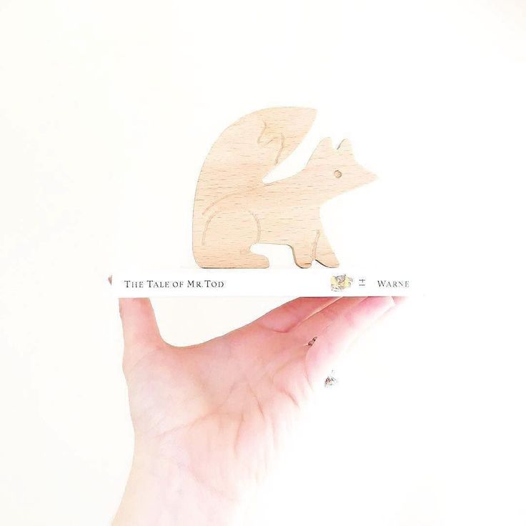 Everyone needs a Clever Fox Natural Wooden Teething Toy in their life  . Loving this gorgeous shot from the super talented talented @georgeandgouma  .  @georgeandgouma via @modernmonty . . . . [stack lay image of an outstretched hand holding a small white children's book on which a fox shaped wooden teething toy is standing.]