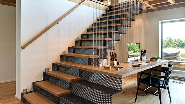 We've seen workspaces placed under the stairs and ones at the top of the stairs, but this workspace takes the combination further, with a desk literally build into and around the stairs.