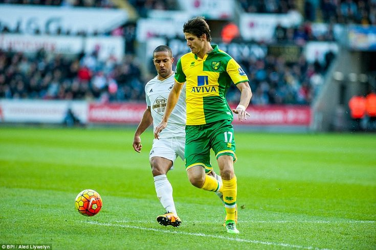 Norwich defenderTimm Klose looks to clear his lines under pressure from Swansea's Routledge but the Canaries were unable to keep a clean sheet.