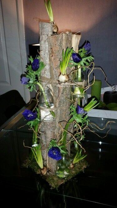 Bloemstuk met boomschors en kleine flesjes. Blauwtint met blauwe druif en anemoon.