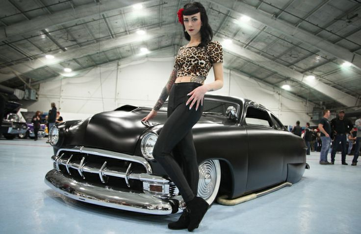 "The beautiful ""Sailor Jassie"", a  Montreal makeup artist and pinup model, poses with one of the vehicles at the Laval Bike and Tattoo show."