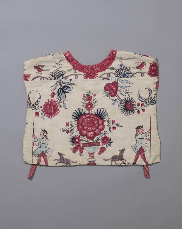 kraplap van sits met figuurscène, Kampereiland Kroplap van 18de eeuwse in India geschilderde katoen met een dessin van mansfiguren in 18de eeuwse westerse kleding ter weerszijden van een bloemenvaas. De kroplap is langs de hals afgewerkt met een gedrukte katoen en gevoerd met linnen. De lussen zijn van gestreept band. De voorzijde is voorzien van koperen ringetjes waarin loss banden met haakjes kunnen worden gehaakt. #Overijssel #Kampen #oudedracht