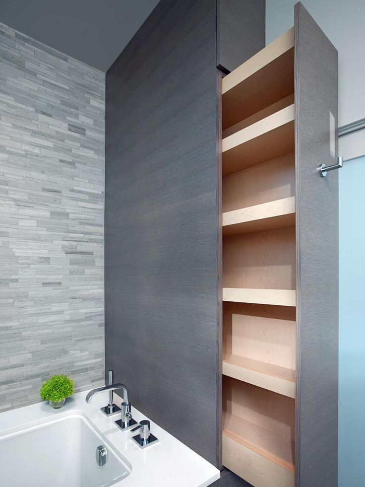 """In a home short on storage, builder Todd Best worked hard to provide his client with plenty of cabinet space. """"She wanted us to be creative,"""" he says. """"So we took advantage of every extra square foot that we could find — thus the use of this custom sliding storage unit in a normally wasted area of their master bathroom."""""""