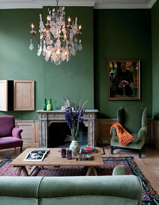 green sitting room with big chandelier