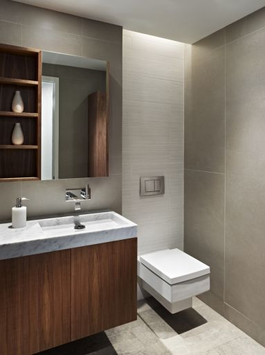 A wall-mounted walnut vanity with marble sink and white textured wall tile in the POWDER ROOM complement  millwork and brick details in an a...