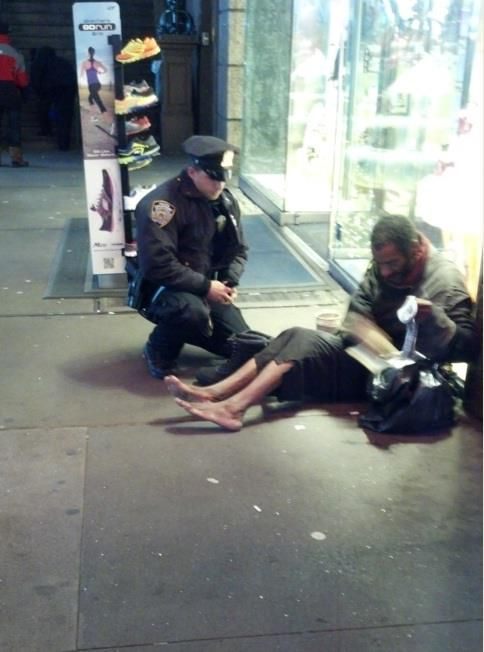 """Larry DePrimo, a NYPD officer, is seen here giving an unidentified homeless man insulated winter boots and thermal socks on a frigid night this month. A tourist from Arizona snapped the photo of the officer without him knowing."""