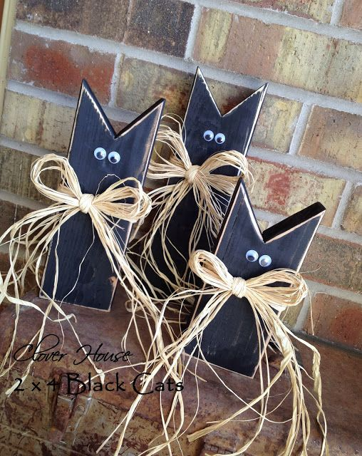 DIY Black Cats.. Too cute! Made of 2 x 4s, Cut, paint, lightly sand and add eyes and raffia!