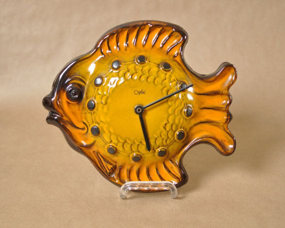 This stunning wall clock was made by the Dutch company Orfac during the seventies. The body of the clock is shaped as a fish. It is such a fun piece, and a great example of Mid Century Modern design, and a great functional item!  The body of the clock has a beautiful yellow and orange glaze, The hours are indicated by raised dots in black. The clock has black coloured hands.  The clock is in great vintage condition. The clock runs on a battery, and is in good working order.  This wonderful…