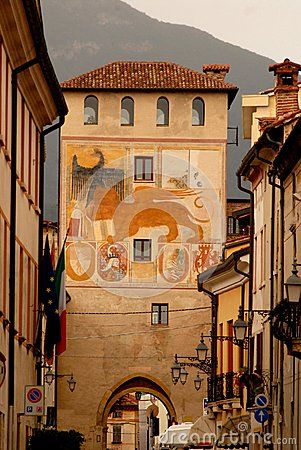 Photo made in Bassano del Grappa, located in the province of Vicenza (Italy). The picture shows the old tower, which is still the south entrance of the city. On the wall of the tower you can see some small ancient frescoes and a recent painting of the winged lion symbol of the republic of Venice. In addition to the tower you can see the outline of one of the mountains that mark the beginning of the Valsugana valley which flows the river Brenta.