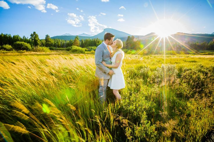 A bride and groom kiss as the sun sets in Estes Park