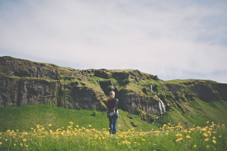 This is Cat standing in front of cliff side that has many waterfalls, one of which is called seljalandsfoss -Iceland
