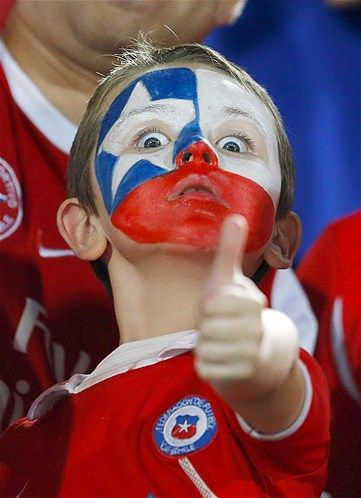 Image: A young fan with his face painted the colors of Chiles national flag gestures before the start of a 2014 World Cup qualifying soccer match against Uruguay in Santiago, Chile, on March 26 (© Victor R. Caivano/AP)
